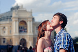 Young happy couple embracing and kissing in city