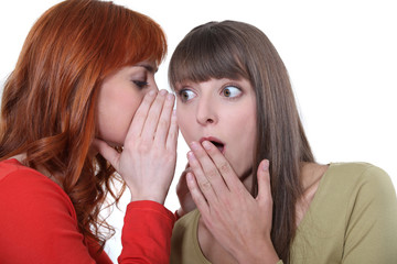 Woman whispering to her friend