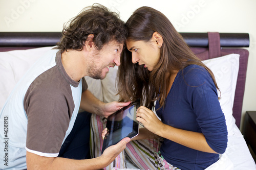 Couple fighting for tablet in bed