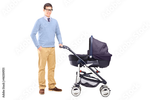 Young father holding a baby stroller