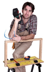 Man posing with workbench and holding an electric screwdriver