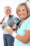 Mature women with tennis rackets