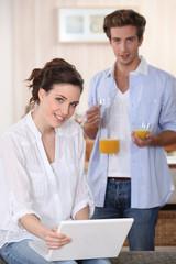 Couple drinking orange juice whilst using laptop