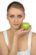 Young woman holding a green apple against her face