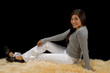 Teen hispanic girl sitting on fur rug