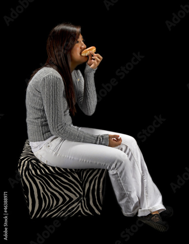 Teen girl eating a donut isolated on a black