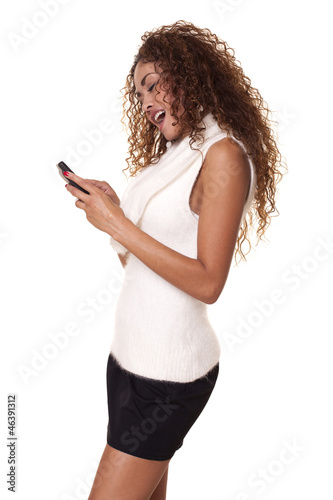 Woman smiles while using her cell phone.