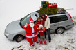 Santa Claus and family with Christmas tree  on the car