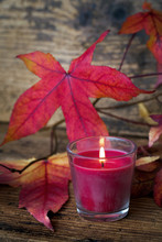 Bougie avec des feuilles rouges