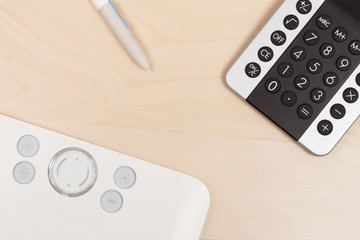 Graphic tablet with calculator on the wooden background