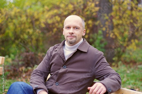 Portrait of the man of average years in autumn park