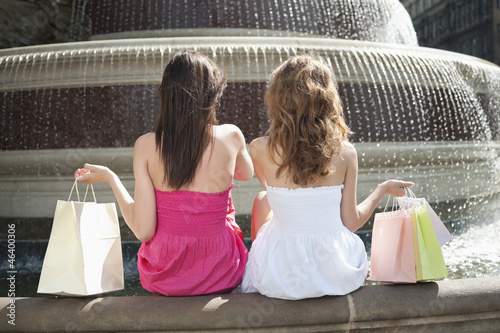 Back view of two young female friends with shopping bags sitting by water fountain