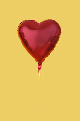 Red heart shaped balloon over yellow background