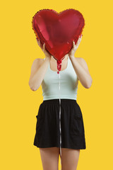 Young woman hiding behind heart shaped balloon over yellow background