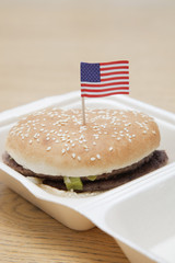 Grilled hamburger with American flag decoration on wooden surface