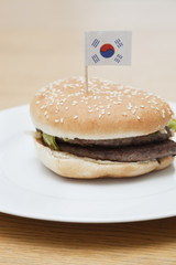 Fresh hamburger in plate with South Korean flag on wooden surface