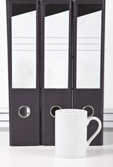 White coffee mug in front of folders at desk