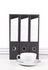 White coffee cup and saucer in front of folders at desk against white wall