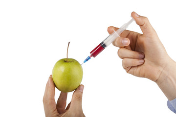 Man's hand injecting granny smith apple against white background