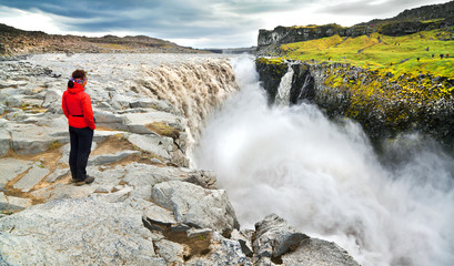 Woman standing near famous Dettifoss waterfall in Iceland