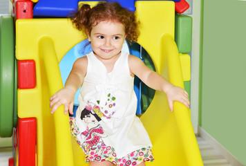 bambina in ludoteca su scivolo