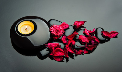 spa background. red petals, stones black and candle
