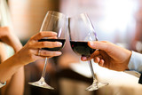 Male and female hands toasting wine glasses.