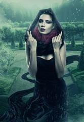 mysterious woman in black hood in garden