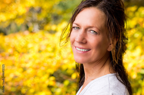 Beautiful Woman in front of Yellow Autumn Tree