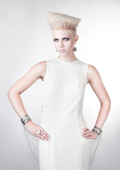 futuristic blond woman in white dress with creative hairstyle