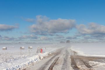 snowy hay bales with road in fog