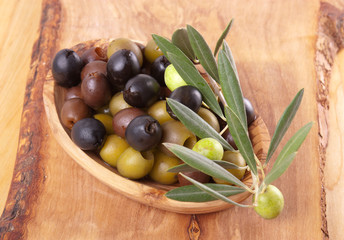 Assorted olives in an wood bowl and an olive twig