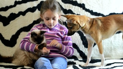 little girl feeding a puppy and a kitten