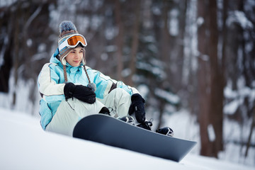 Girl with snowboard taking a break