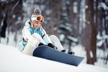 Young woman strapping on Snowboard