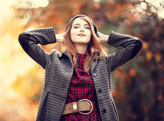 Style redhead girl at beautiful autumn alley.