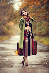 Style redhead girl with suitcase at beautiful autumn alley.