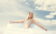 Young blond woman in white dress on background of the sky