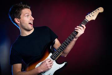 junger mann spielt ausgelassen auf einer gitarre