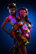Couple women with glow uv body art and flowers