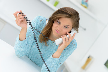frustrierte junge frau am telefon
