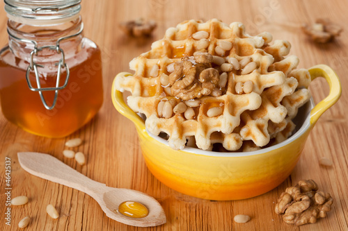 Sweet Belgian waffles with honey and nuts for a tasty breakfast