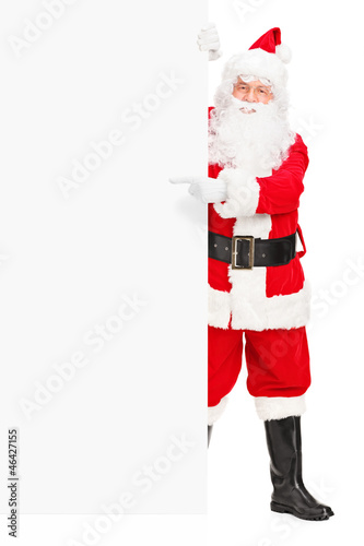 Santa claus posing next to a billboard and pointing