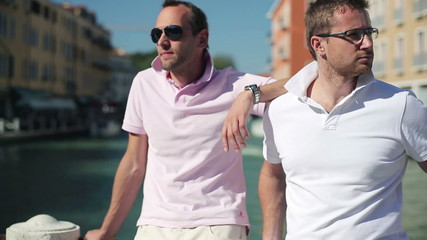 Two male friends smiling to camera in Venice, crane shot