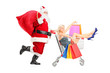 Santa Claus pushing a young woman in a shopping cart