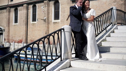 Just married couple talking on cellphone in Venice, crane shot