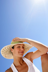 Woman in a straw hat against a blue sky