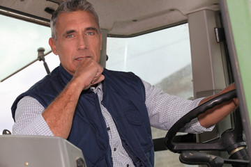 a farmer in a tractor cabin is driving
