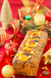Christmas Fruit-cake with festive decoration, on red