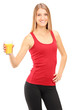 Female athlete holding a orange juice, refreshing after an exerc